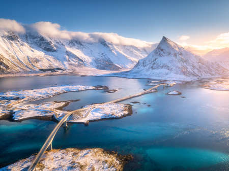 Aerial view of bridge over the sea and snowy mountains in Lofoten Islands, Norway. Fredvang bridges at sunset in winter. Landscape with blue water, rocks in snow, road and sky with cloads. Top view
