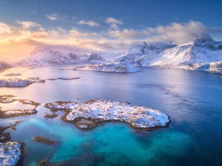 Aerial view of Lofoten islands in winter at sunset in Norway. Landscape with blue sea, snowy mountains, rocks and islands, colorful sky with clouds and orange sunlight at cold evening. Top view.