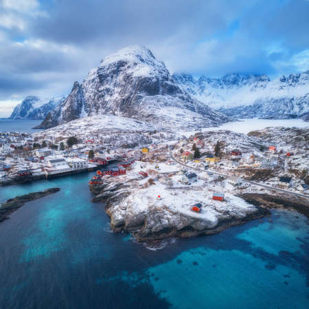 Landscape with blue sea, snowy mountains, high rocks, buildings, traditional rorbu, cloudy sky. Aerial view of small village at sunset in winter. Travel in Lofoten islands, Norway. View from above 免版税图像