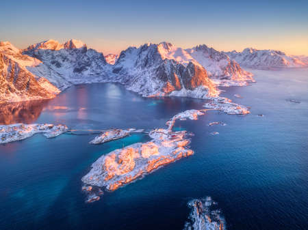 Beautiful landscape with clear blue sea, snowy mountains, rocks and islands, village, buildings, road, bridge. Aerial view of Hamnoy in snow at sunrise in winter in Lofoten islands, Norway. Top view 免版税图像