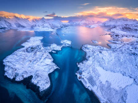 Aerial view of Lofoten islands in winter at sunset in Norway. Landscape with blue sea, snowy mountains, rocks and islands, road, bridge, village, buildings, colorful sky with pink clouds. Top view