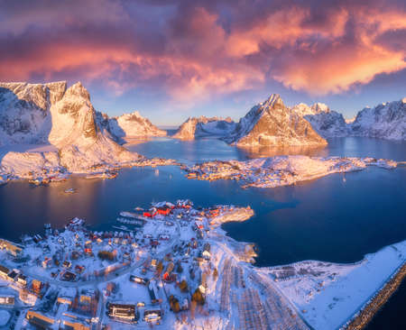 Colorful landscape with blue sea, snowy mountains, high rocks, village with buildings, rorbu, sky with pink clouds. Aerial view of Reine at sunrise in winter. Top view of Lofoten islands, Norway