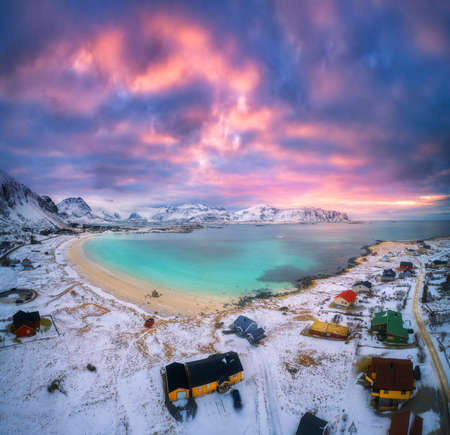 Aerial view of nordic sandy beach with blue sea in winter at sunset in Lofoten islands, Norway. Landscape with snowy coast. mountains, colorful sky, water, village with buildings. Nature. Top view