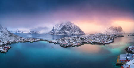 Aerial view of blue sea, snowy mountains, high rocks, village with buildings, rorbu, colorful sky, reflection in azure water. Reine at sunset in winter. Top view of Lofoten islands, Norway. Landscape