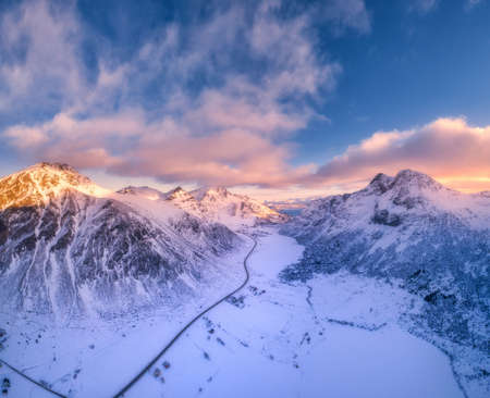 Beautiful snowy mountains in winter at sunset. Aerial view. Lofoten Islands, Norway. Colorful landscape with road, rocks in snow, houses and blue sky with sunlight and pink clouds. Top view. Nature