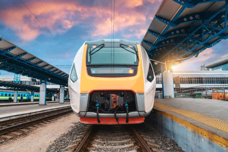 High speed train on the railway station at sunset. Industrial landscape with moving modern intercity passenger train on the railway platform, buildings. Railroad in Europe. Commercial transportation