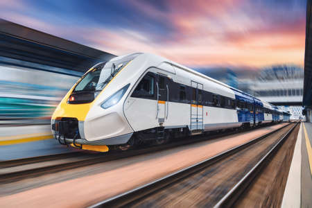High speed train in motion on the railway station at sunset. Modern intercity passenger train with motion blur effect on the railway platform. Industrial. Railroad transportation in Europe. Industry