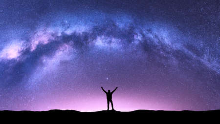 Arched Milky Way and happy man at night. Silhouette of guy with raised up arm on the hill, purple sky with stars, pink light in summer. Galaxy. Space background. Landscape with milky way arch. Travel