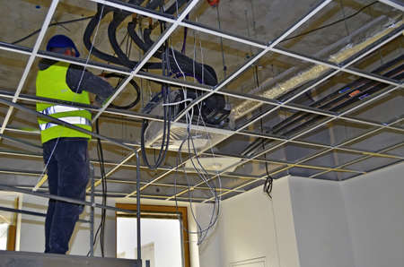 Besançon, France - April 9, 2015: Workman installing wirings under a suspended ceiling on a construction site.