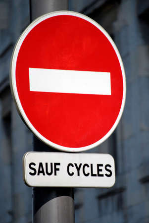 """French """"prohibited direction except for cycles"""" road sign with a building in the background"""