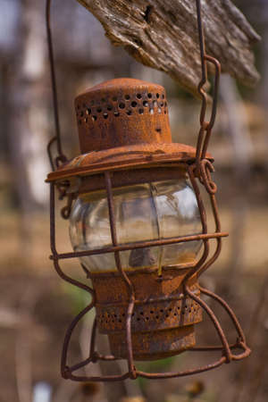 An Old Rusty Oil Lamp hanging on a wood fence.