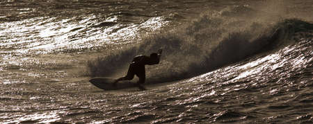A surfer is riding a wave by sunset along beautiful Oahu, Hawaii North Shore 版權商用圖片