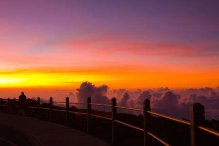 A man is witnessing the unforgettable beauty of a sunset viewed from the top of the Haleakala Vocalno, Maui, Hawaii photo