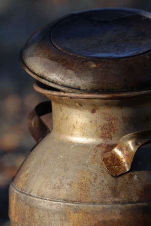 An antique milk container, aged and rusted by the passage of time