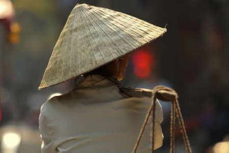 mekong: A vietnamese woman, wearing a traditional hat, is starting a long day of work under the hot and sweaty sun of Hanoi. Stock Photo