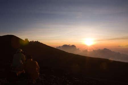Two hikers are witnessing a beautiful sunset at the top of Haleakala volcano. Maui, Hawaii. 版權商用圖片