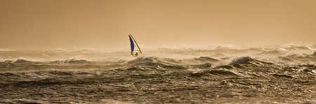 A windsurfer rides along the beautiful Maui's shores  a few minutes before sunset. 版權商用圖片