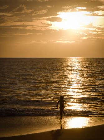 A young girl is having fun running on a sandy beach at sunset on beautiful Hawaii, Maui 版權商用圖片