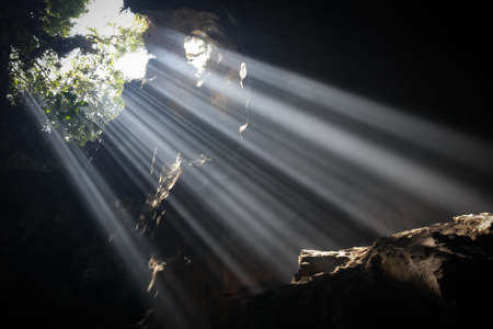 Multiple light beams are illuminating the bottom of a cave near Hanoi, North Vietnam.