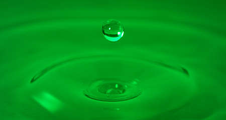 Drop of water captured with high speed macro photo with - Green gel filter- Shallow depth of field - Horizontal
