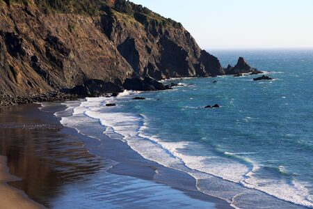mountain bicycling: Pacific Coast: Layers of ocean waves on wide sandy beach at coastline mountains California