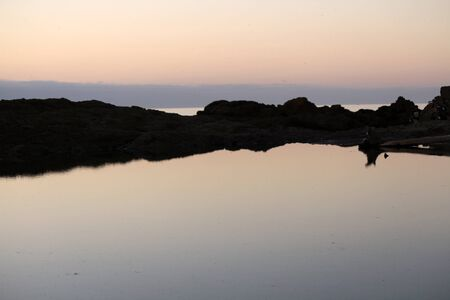 evening glow: Evening glow on water at sunset over mountain coast Stock Photo