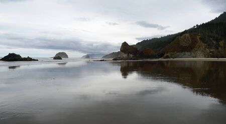 oregon coast: Oregon coast reflection of rocks and sky on expansive coast Stock Photo
