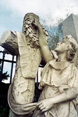 reaching up: angel statue reaching up to put wreath on cross Editorial