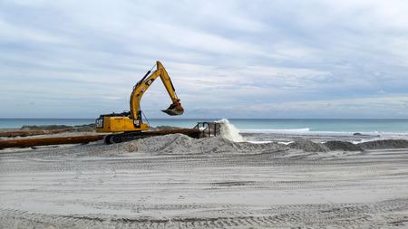 Crane and beach sand restoration equipment to reverse beach erosion.