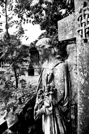 angel cemetery: Life size angel statue, profile of beautiful serene angel with flowers in cemetery near majestic cross medieval embossed emblem, black  white photograph. Stock Photo