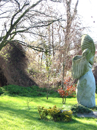 sorrowful: Angel statue in garden grass, hides under wing, appears to float when viewer walks further back from photo. Stock Photo
