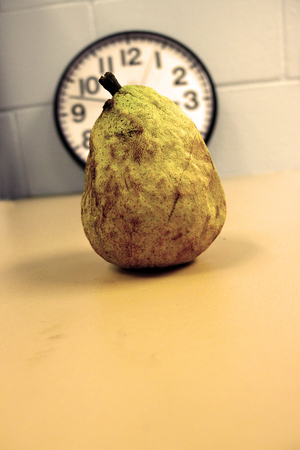rotting: Yellow brown rotting pear with shadow sitting in front of a clock watching time.