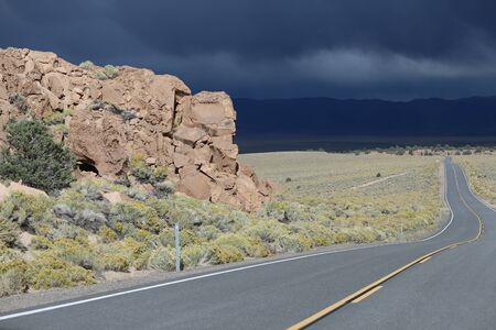 inclement weather: Large red rock formation near winding road with yellow divider line leading into dark rain clouds over blue mountains