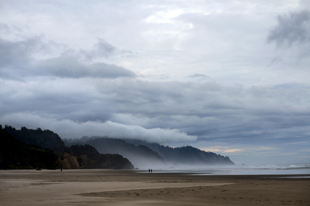 oregon coast: Oregon Coast with mist from ocean and layered clouds above mountains and expansive beach