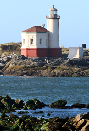 Lighthouse on coastline of blue water and rocky shore during mid morning sun.