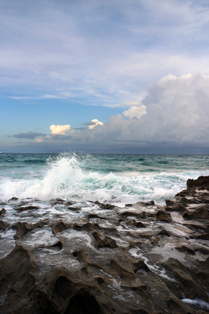 Rolling ocean waves of teal hues pounding against rocky cratered shoreline Stock Photo