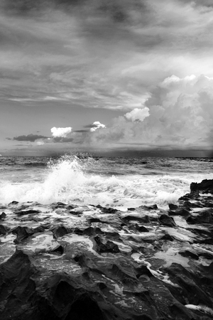 nature photo: Black and White photo of white caps and waves crashing on the ocean rocks beneath a heavy layered grey sky of clouds.