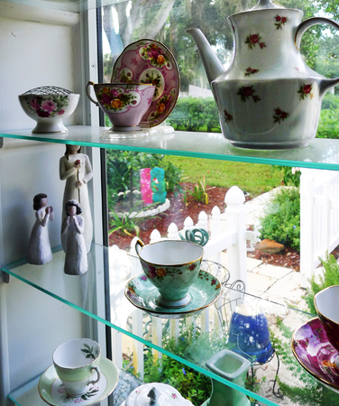 treasured: Glass shelf of treasured teacups, teapot and figurines looking onto beautiful country garden.