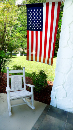 homestyle: American flag overhanging on porch with childs wicker rocking chair in country front yard. Stock Photo
