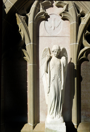 felice: Angel statue in daylight with dove of peace emblem above her head.