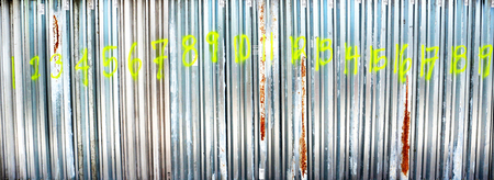A line of Hurricane Storm Shutters in a row marked with the numbers 1 thru 19 in neon green spray paint... counting the days to pass.