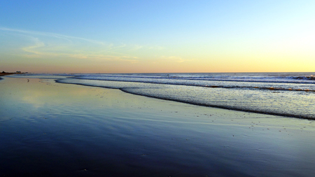 Beautiful Awe Inspiring Morning Sunrise Glow on Layered Ocean Tide Ripples and Wet Sandy Beach
