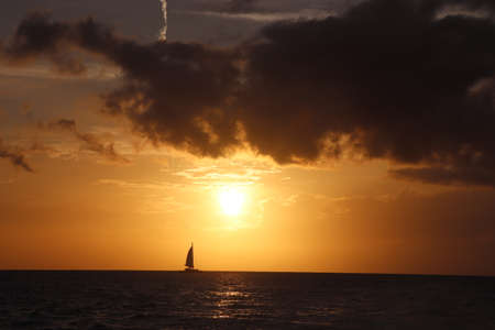 Sailboat sails into the sunset 스톡 콘텐츠