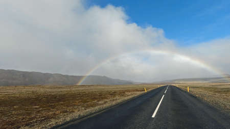 Rainbow across the road in Iceland 스톡 콘텐츠