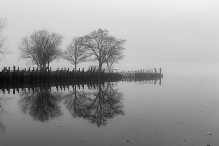 Mysterious park on the foggy river
