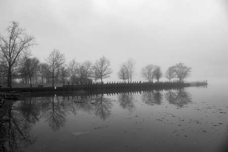 Scenic pier on reflected in a river on a foggy day