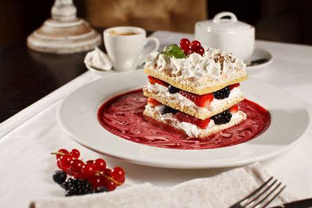 食欲をそそるフランス millefeuilles ラズベリー、ブラックベリー、イチゴのデザートとコーヒー