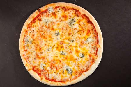 queso: Vista superior sabrosa pizza italiana sobre un fondo oscuro
