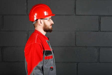 casco rojo: vista lateral de un mono que llevan los trabajadores y casco rojo y gafas de protección