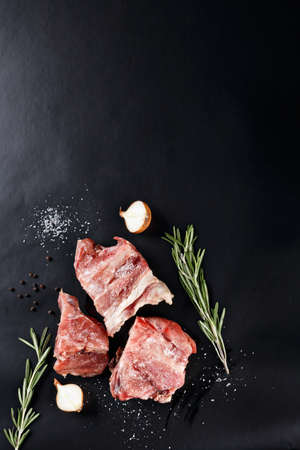 frozen meat: slices of frozen meat with rosemare and onion on black paper Stock Photo